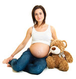 Brunette pregnant woman with teddy Stock Photo