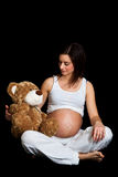 Brunette pregnant woman with teddy Stock Photography