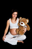 Brunette pregnant woman with teddy bear on black Royalty Free Stock Images