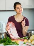 Brunette preparing pork ribs Royalty Free Stock Photography