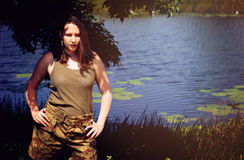 Brunette pretending to be a soldier. On the grass on a farm or in a park Royalty Free Stock Image