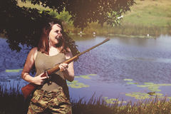 Brunette pretending to be a soldier. On the grass on a farm or in a park Royalty Free Stock Photography