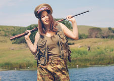 Brunette pretending to be a soldier. On the grass on a farm or in a park Stock Images