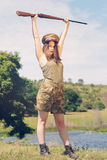 Brunette pretending to be a soldier. On the grass on a farm or in a park Royalty Free Stock Images