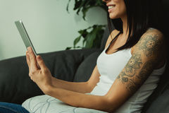 Brunette pretty girl with a tattoo looking a tablet Royalty Free Stock Photo
