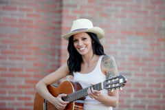Brunette pretty woman playing a guitar Stock Images