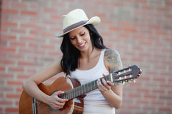 Brunette pretty woman playing a guitar Stock Photography