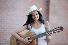 Brunette pretty woman playing a guitar Royalty Free Stock Photos