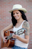 Brunette pretty woman playing a guitar Stock Photos