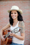 Brunette pretty woman playing a guitar Royalty Free Stock Image