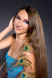 Brunette professionally makeup girl. Beautiful professionally makeup smiling girl with long brown hair wearing blue dress with peacock feather stock photos