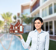 Brunette property agent presents a new house for sale. Beautiful brunette property agent presents a new house for sale. Luxury villa in blur as a background Stock Photography