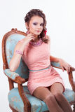 Brunette with purple make-up in pink dress sitting on a chair in. Portrait of curly brunette with purple make-up in pink dress with pink soutache technique stock photography