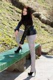 Brunette putting heel on bench Royalty Free Stock Image