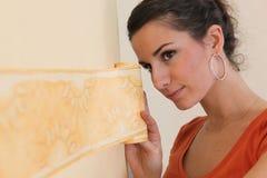 Brunette putting up decorative sticker Stock Photo
