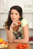 Brunette que cocina en cocina Imagen de archivo libre de regalías