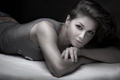 Brunette que coloca em sua cama Foto de Stock Royalty Free