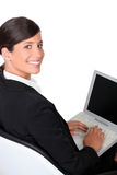 Brunette que datilografa no teclado do portátil Imagem de Stock