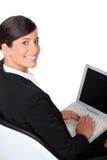 Brunette que pulsa en el teclado de la computadora portátil Imagen de archivo