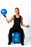 Brunette que se sienta en bola de la aptitud con el blueball Fotografía de archivo libre de regalías