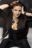 Brunette que senta-se em um sofá branco Fotos de Stock Royalty Free
