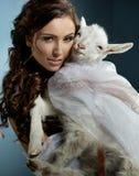 brunette que sostiene una pequeña cabra Imagen de archivo libre de regalías