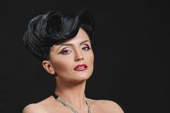 Brunette quiff. Portrait of beautiful girl with elegant coiffure quiff on black Stock Image