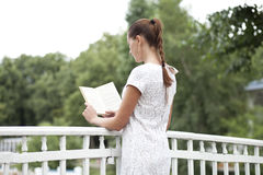 Brunette reading book in a summer park Stock Photos