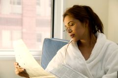 Brunette reading the morning papers. Attractive young brunette in a bath robe reads the morning paper Royalty Free Stock Images