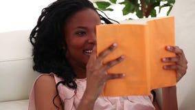 Brunette reading a novel. In the living room stock video