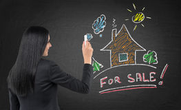 Brunette real estate agent is drawing a new colourful house on the black chalkboard. Royalty Free Stock Photos