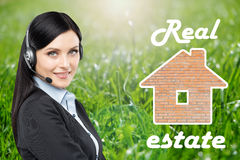 Brunette real estate agent is in a headset and a picture of the bricks house. Royalty Free Stock Image