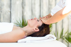 Brunette receiving forehead massage Royalty Free Stock Images