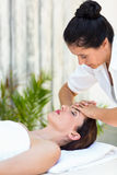 Brunette receiving forehead massage Royalty Free Stock Image