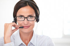 Brunette receptionist speaking on the headphones Stock Images