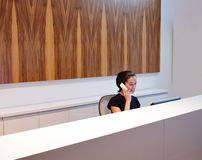 Brunette receptionist young woman in desk Royalty Free Stock Photos