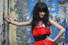 Brunette in red. The girl in a red dress on a background of an old concrete wall stock image