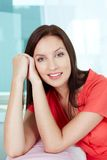Brunette in red. Portrait of a smiling woman in red clothing looking at camera Stock Image