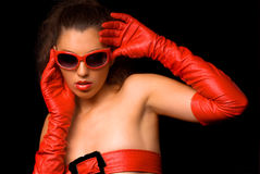 Brunette in red. Glasses, red gloves and with red belt on breasts on the black background Stock Photography