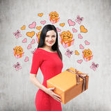 A brunette in red dress holds an orange gift box. Royalty Free Stock Photography
