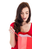 Brunette in red dress looking in shopping bag Stock Photography
