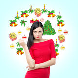 A brunette in red dress is waiting for Christmas and New Year's Eve. Christmas-tree decorations are drawn on the light blue backgr Stock Photos