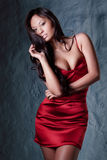 Brunette in red evening dress. Young gorgeous brunette in red evening dress posing stock photo