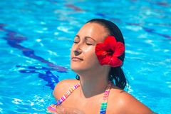 Brunette with red flower on sun holidays. Beautiful brunette with red flower on sun holidays Royalty Free Stock Photos