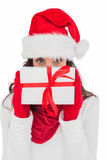 Brunette in red gloves and santa hat showing gift Stock Images