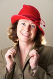 Brunette in red hat holding jacket lapels Royalty Free Stock Photography