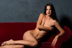 Brunette on a red sofa Royalty Free Stock Photography