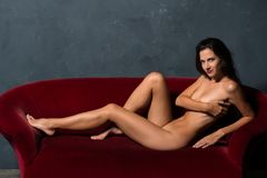 Brunette on a red sofa Royalty Free Stock Image