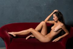 Brunette on a red sofa Stock Photo