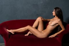 Brunette on a red sofa Royalty Free Stock Photos